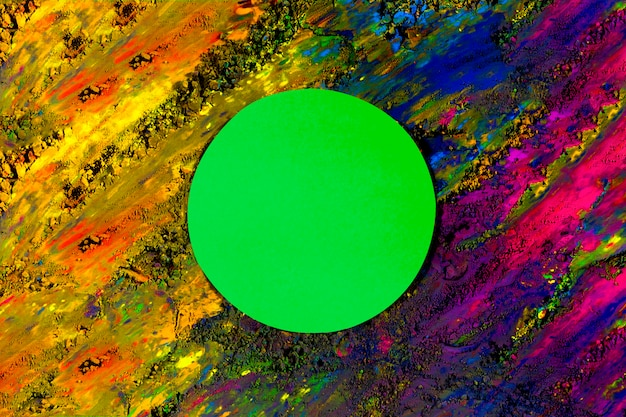 Green circle paper frame on smudged dry holi colored