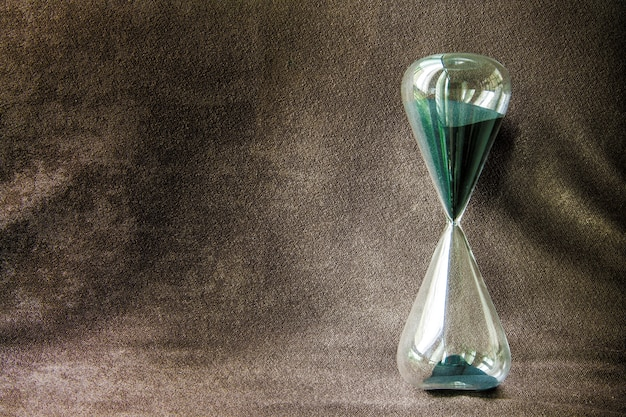 Green classic sandglass and brown background