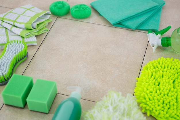 Green cleaning products arranged on tiled floor