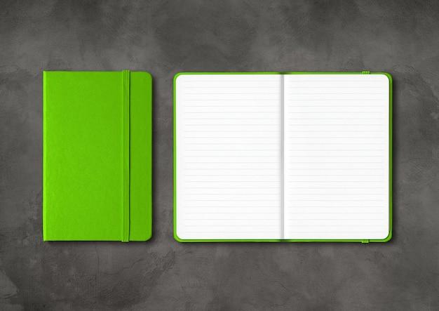 暗いコンクリートの背景に分離された緑の閉じた、開いた裏地付きノートブックのモックアップ