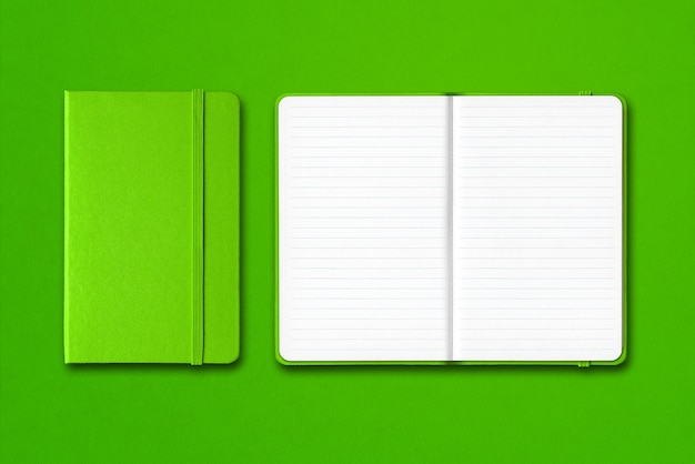 Green closed and open lined notebooks isolated
