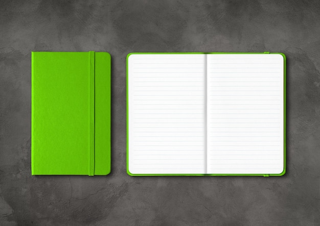 Green closed and open lined notebooks mockup isolated on dark concrete background