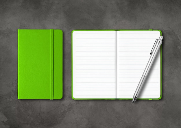 Green closed and open lined notebooks with a pen on concrete table.