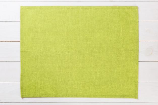コピースペースを持つ白い素朴な木製トップビューに緑の布ナプキン