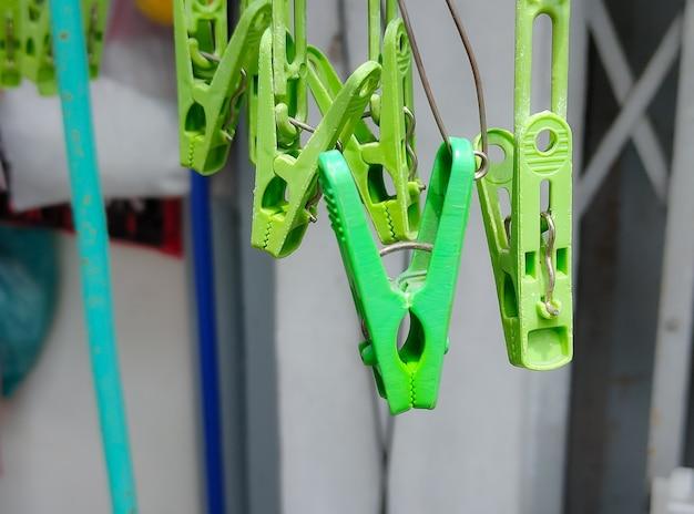 洋服を掛けるのにすぐに使える緑色の洗濯バサミ。