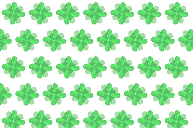 緑のクローバーの葉は、白い壁に色紙から手作りされた4枚の花びらの紙です。幸せな聖パトリックの日のコンセプト。
