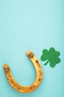 聖パトリックの日の休日のための青い背景の上の緑のクローバーと金の馬蹄形。上面図。