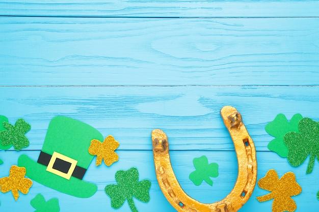 聖パトリックの日の休日のための青い木製の背景に緑のクローバーと金の馬蹄形。上面図。