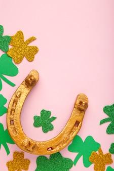 聖パトリックの日の休日のためのピンクの壁に緑のクローバーと金の馬蹄形。上面図。