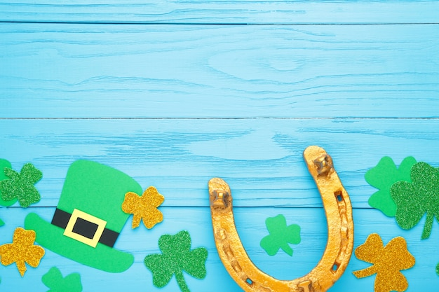 Green clovers and gold horseshoe on blue wooden background for st. patrick's day holiday. top view.