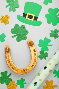 Green clovers and gold horseshoe on grey background for st. patrick's day holiday. top view.