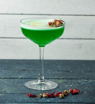 Green cocktail in crystal glass garnished with dried rose buds