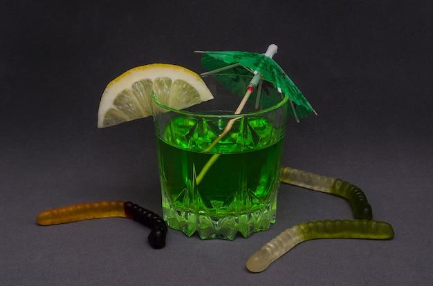 Зеленый коктейль на хэллоуин, украшенный долькой лимона и декоративным зонтиком