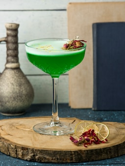 Green cocktail garnished with dried rose buds in crystal glass