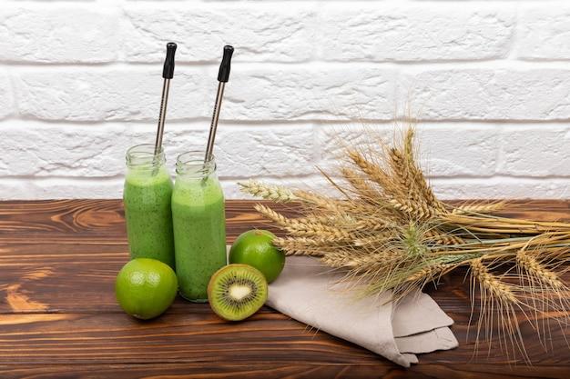 Зеленый коктейльный смузи из шпината в стеклянном соке смузи на столе