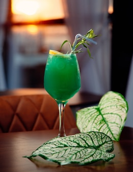 Green cocktail with lemon slice and mint leaves.
