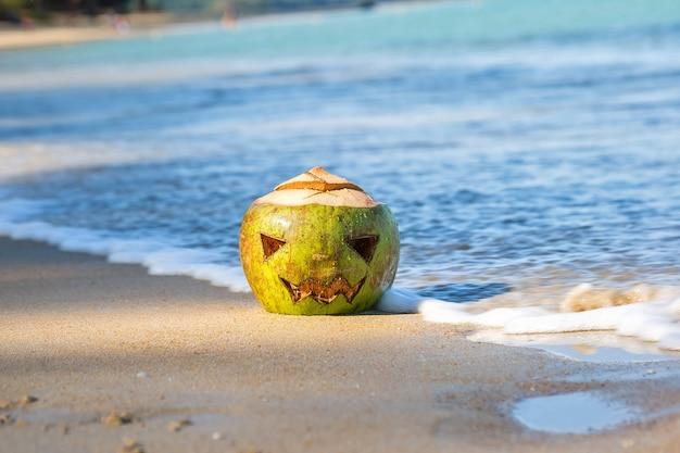 Лицо зеленого кокоса, вырезанное в виде тыквы на хэллоуин. лежит в песке на тропическом пляже.