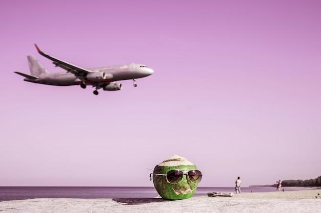 Зеленый кокос в солнцезащитных очках на пляже тыква в форме для хэллоуина взлетает с самолета