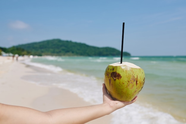 Green coconut with drinking straw