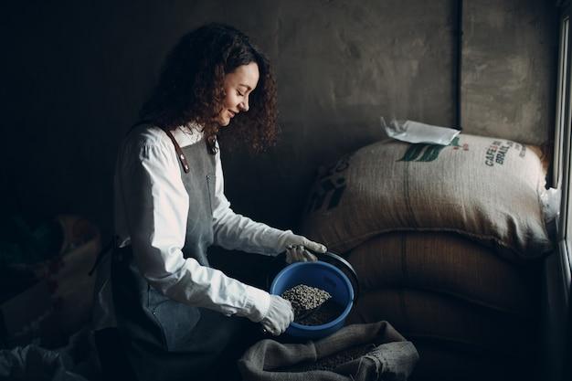 黄麻布の袋とスクープと女性のロースターの緑のコーヒー豆。