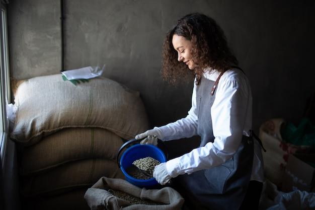 黄麻布の袋とスクープと女性労働者のロースターの緑のコーヒー豆