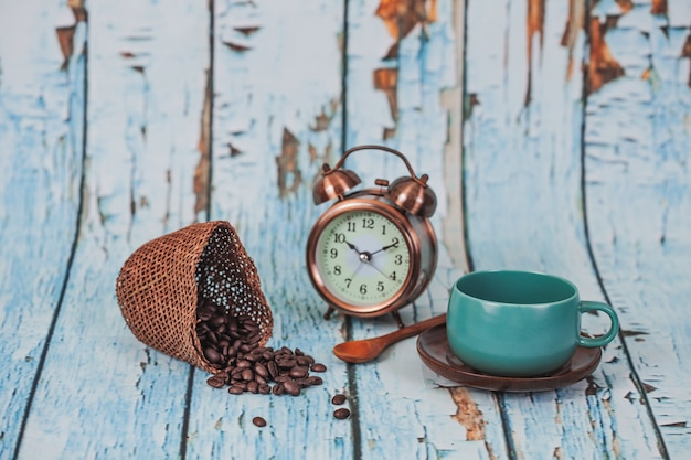 Green coffee cup and coffee beans on old wood background