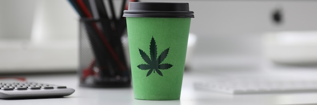Green coffee cup with cannabis logo on office tabl