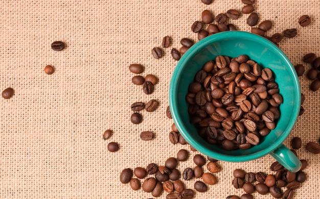 Зеленая кофейная чашка с зернами и фоном ткани из рафии