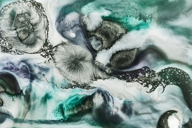Green color alcohol ink background, abstract ocean. exoplanet surface, marble texture, fluid liquid background. stains and streaks of paint under water