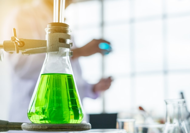 Green color glass measuring beaker with scientist background in a laboratory.