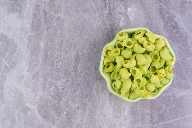 Домашние пасты зеленого цвета в тарелке на мраморе.