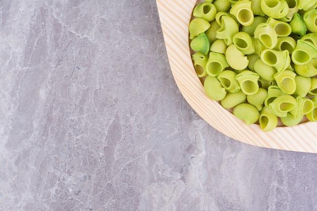 Paste fatte in casa di colore verde in un piatto sul marmo.