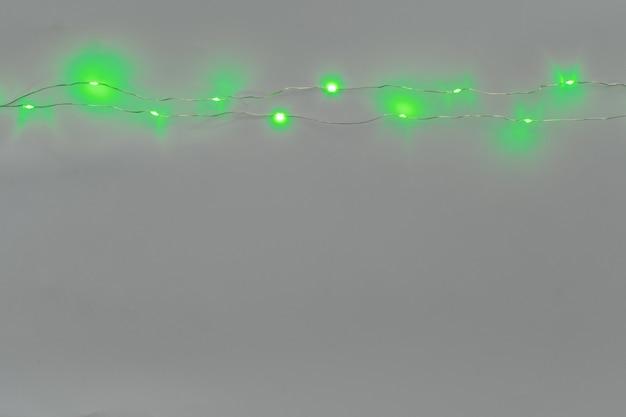 밝은 회색 배경에 녹색 조명 화환