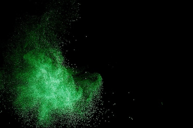 Green color powder explosion cloud on black background. green dust splash.