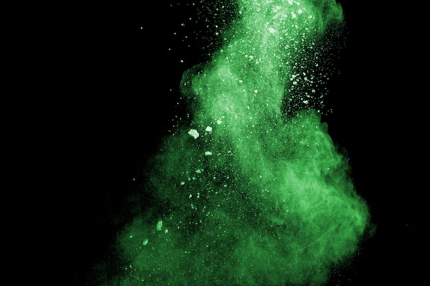 Green color powder explosion cloud  on black background.