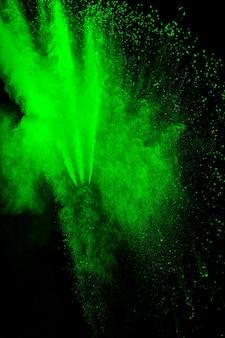 Облако взрыва порошка зеленого цвета на черном фоне. всплеск зеленой пыли на фоне.