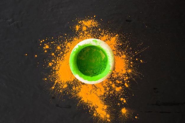 검은 배경에 노란색 가루 튄와 그릇에 녹색 분말