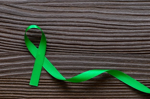 Green color ribbon on dark wooden background.