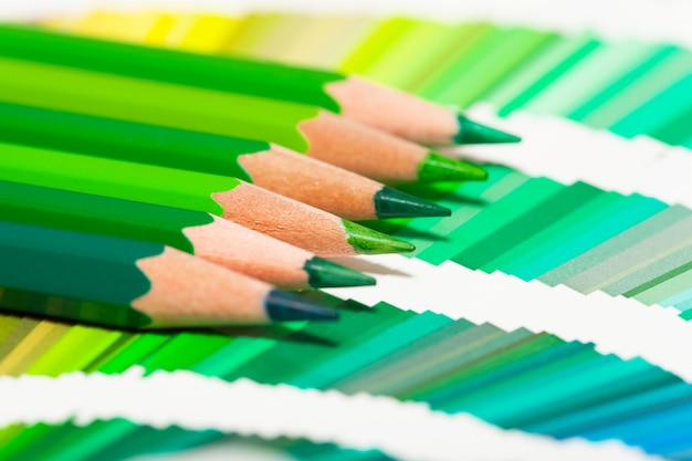 Green colored pencils and color chart of all colors