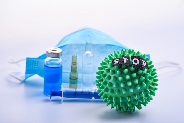 緑のカラフルな明るい孤立した先端のとがったボールグッズテキストストップと医療マスクとアンプル。薬はウイルスを止めます