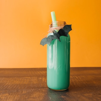 Green colour drink in bottle with handmade bat on orange background
