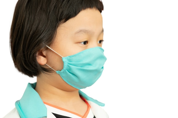Green colour surgical protect mask on asia kid doctor dress face ,look at camera ,headshot portrait ,isolated on white,side view