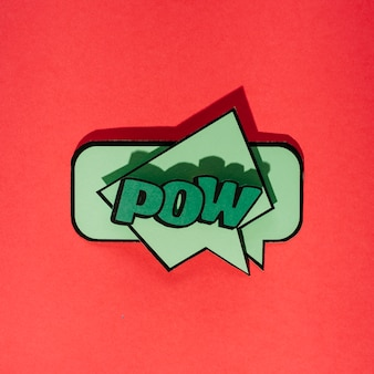 Green comic speech bubble with expression text pow on red background