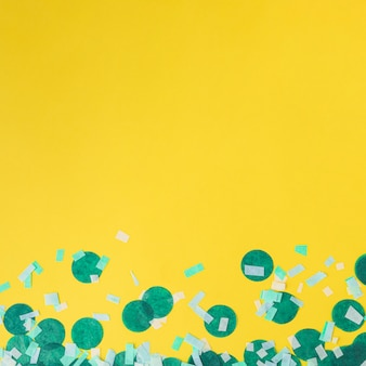 Green confetti on yellow background with copy space