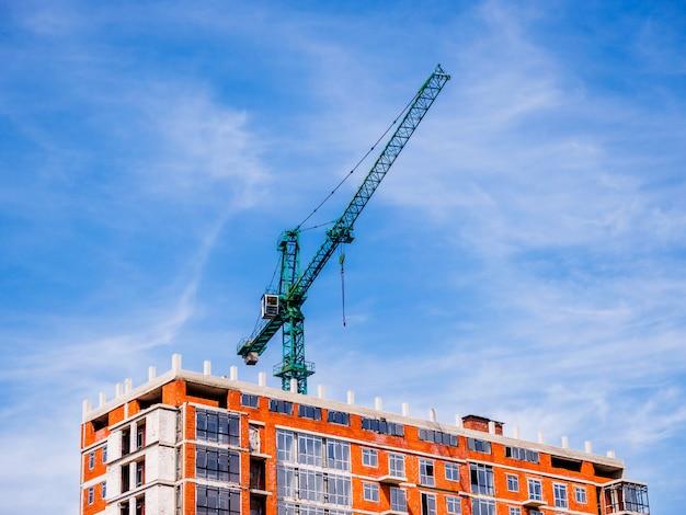Зеленый строительный кран с фоном голубого неба