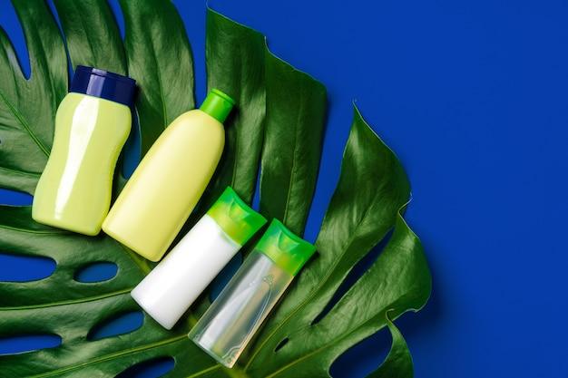 Зеленая косметическая бутылка и лист монстера на синем фоне