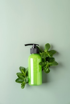 Зеленая косметическая бутылка с дозатором, свежая мята на пастельно-зеленом фоне. концепция органической косметики. макет косметического контейнера с местом для текста. натуральный продукт по уходу за кожей.