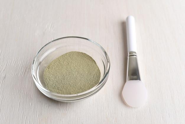 Зеленая косметическая глина в тазике и кисточка для нанесения маски на лицо.