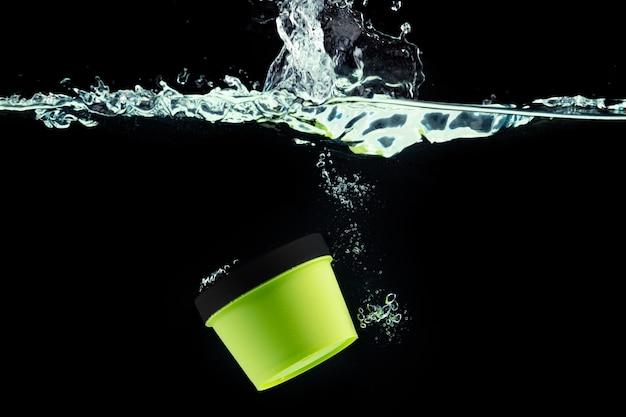Зеленая косметическая банка, ныряющая в воду на черном фоне