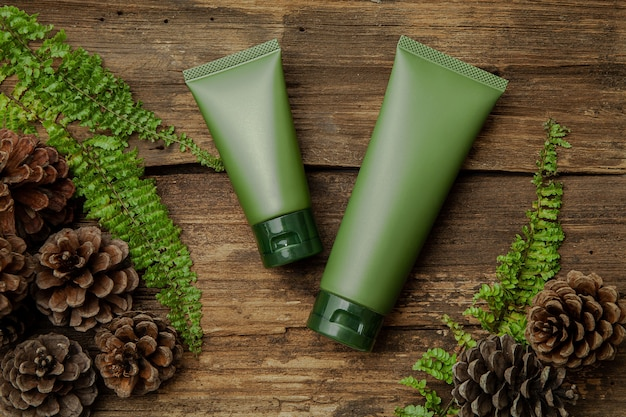 Green cosmetic tubes with green leaves on wood